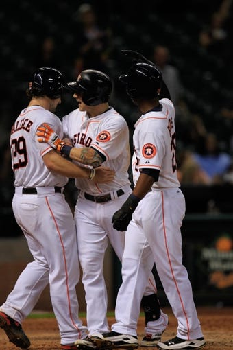 Sep 3, 2013; Houston, TX, USA; Houston Astros center fielder Brandon Barnes (2) and first baseman Brett Wallace (29) and right fielder L.J. Hoes (28) celebrates scoring runs against the Minnesota Twins during the ninth inning at Minute Maid Park. Mandatory Credit: Thomas Campbell-USA TODAY Sports
