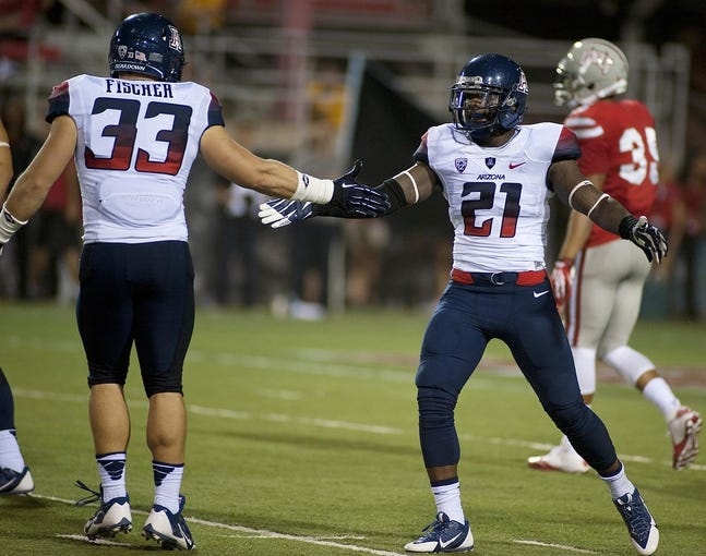 Sep 7, 2013; Las Vegas, NV, USA; Arizona Wildcats linebacker Jake Fischer celebrates with safety Tra'Mayne Bondurant after a defensive stop against the UNLV Rebels at Sam Boyd Stadium. Arizona won the game 58-13. Mandatory Credit: Stephen R. Sylvanie-USA TODAY Sports