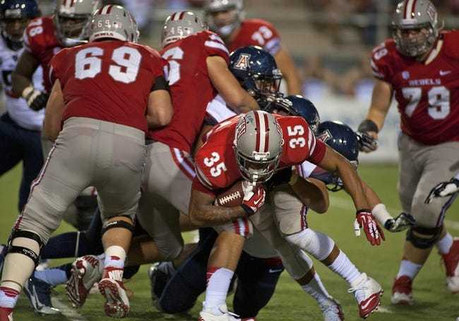 Sep 7, 2013; Las Vegas, NV, USA; UNLV Rebels running back Tim Cornett tries to break a tackle at the line against the Arizona Wildcats at an NCAA football game at Sam Boyd Stadium. Arizona won the game 58-13. Mandatory Credit: Stephen R. Sylvanie-USA TODAY Sports