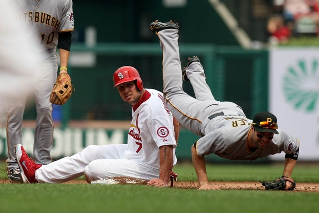 Sep 8, 2013; St. Louis, MO, USA; Pittsburgh Pirates second baseman Neil Walker (18) falls over St. Louis Cardinals left fielder Matt Holliday (7) as he attempts to turn a double play at Busch Stadium. Mandatory Credit: Scott Kane-USA TODAY Sports