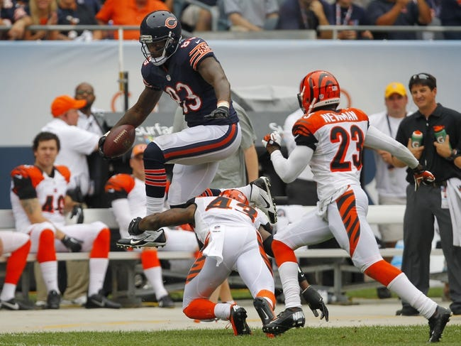 Sep 8, 2013; Chicago, IL, USA; Chicago Bears tight end Martellus Bennett (83) leaps over Cincinnati Bengals free safety George Iloka (43) during the second half at Soldier Field. Chicago won 24-21. Mandatory Credit: Dennis Wierzbicki-USA TODAY Sports