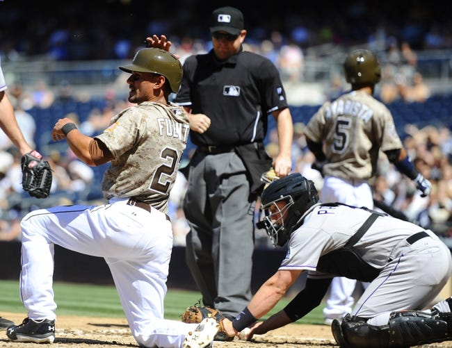 Sep 8, 2013; San Diego, CA, USA; San Diego Padres center fielder Reymond Fuentes (27) reacts after being tagged out by Colorado Rockies catcher Jordan Pacheco (15) while trying to score on a passed ball during the third inning at Petco Park. Mandatory Credit: Christopher Hanewinckel-USA TODAY Sports
