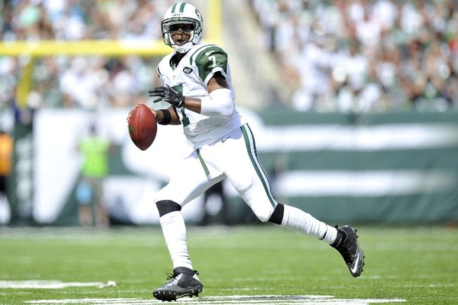 Sep 8, 2013; East Rutherford, NJ, USA; New York Jets quarterback Geno Smith (7) scrambles against the Tampa Bay Buccaneers during the first half at MetLife Stadium. The Jets won 18-17. Mandatory Credit: Joe Camporeale-USA TODAY Sports