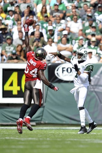 Sep 8, 2013; East Rutherford, NJ, USA; New York Jets quarterback Geno Smith (7) throws a pass past the reach Tampa Bay Buccaneers outside linebacker Lavonte David (54) during the first half at MetLife Stadium. The Jets won 18-17. Mandatory Credit: Joe Camporeale-USA TODAY Sports
