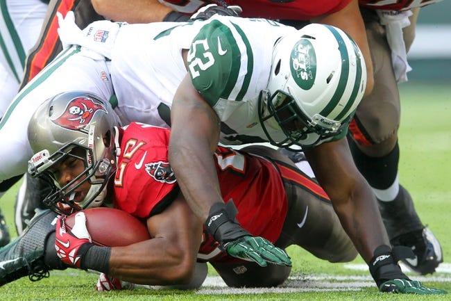 Sep 8, 2013; East Rutherford, NJ, USA; Tampa Bay Buccaneers running back Doug Martin (22) is tackled by New York Jets linebacker David Harris (52) during the first quarter of a game at MetLife Stadium. The Jets won 18-17. Mandatory Credit: Brad Penner-USA TODAY Sports