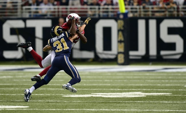 Sep 8, 2013; St. Louis, MO, USA; Arizona Cardinals wide receiver Andre Roberts (12) catches a pass for 8 yards as St. Louis Rams cornerback Cortland Finnegan (31) defends during the second half at Edward Jones Dome. St. Louis defeated Arizona 27-24. Mandatory Credit: Jeff Curry-USA TODAY Sports