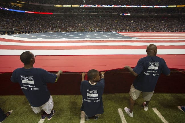Sep 8, 2013; St. Louis, MO, USA; Fans hold the flag before the game against the Arizona Cardinals at Edward Jones Dome. The Rams defeated the Cardinals 27-24. Mandatory Credit: Scott Rovak-USA TODAY Sports