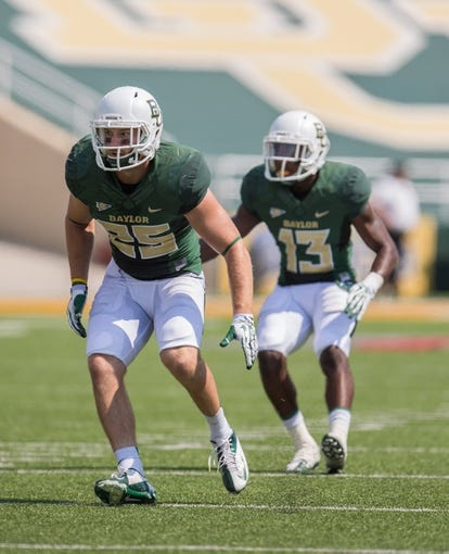 Sep 7, 2013; Waco, TX, USA; Baylor Bears defensive back Sam Holl (25) and safety Terrell Burt (13) face the Buffalo Bulls attack during the game at Floyd Casey Stadium. The Bears defeated the Bulls 70-13. Mandatory Credit: Jerome Miron-USA TODAY Sports
