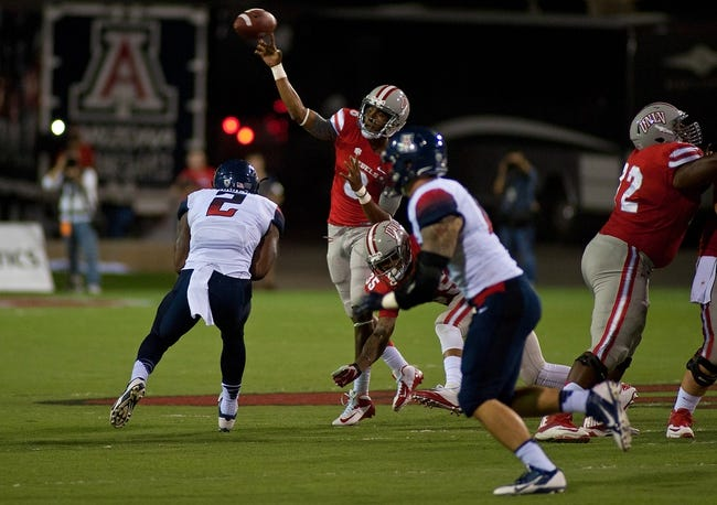 Sep 7, 2013; Las Vegas, NV, USA; UNLV Rebels back up quarterback Caleb Herring makes a pass attempt under pressure from Arizona Wildcats linebacker Marquis Flowers at Sam Boyd Stadium. Arizona won the game 58-13. Mandatory Credit: Stephen R. Sylvanie-USA TODAY Sports