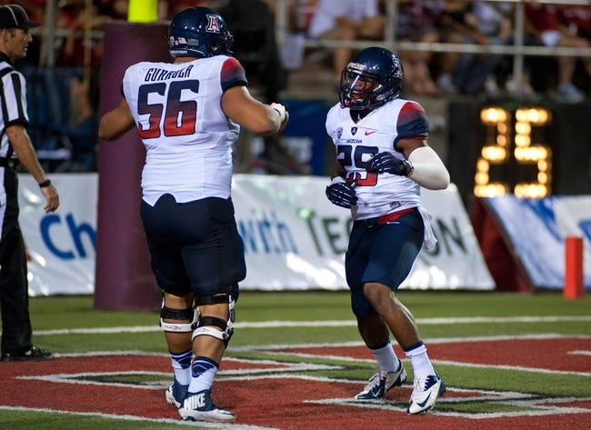 Sep 7, 2013; Las Vegas, NV, USA; Arizona Wildcats running back Ka'Deem Carey, right, celebrates with offensive lineman Steven Gurrola after scoring a touchdown against the UNLV Rebels at Sam Boyd Stadium. Arizona won the game 58-13. Mandatory Credit: Stephen R. Sylvanie-USA TODAY Sports