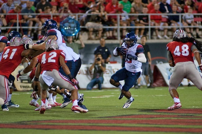 Sep 7, 2013; Las Vegas, NV, USA; Arizona Wildcats running back Ka'Deem Carey runs the ball through the Rebels defense during an NCAA football game at Sam Boyd Stadium. Carey rushed for 171 yards scoring two touchdowns against the Rebels, leading the Wildcats to a 58-13 victory. Mandatory Credit: Stephen R. Sylvanie-USA TODAY Sports