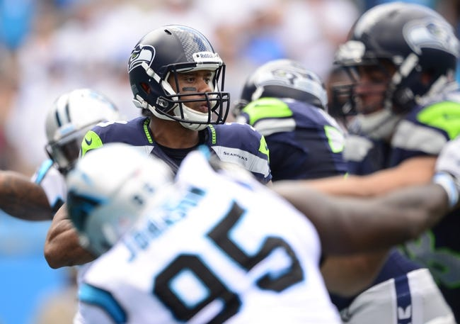 Sep 8, 2013; Charlotte, NC, USA; Seattle Seahawks quarterback Russell Wilson (3) looks to pass as Carolina Panthers defensive end Charles Johnson (95) defends in the first quarter. The Seahawks defeated the Panthers 12-7 at Bank of America Stadium. Mandatory Credit: Bob Donnan-USA TODAY Sports