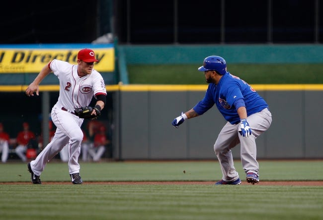Sep 9, 2013; Cincinnati, OH, USA; Cincinnati Reds shortstop Zack Cozart (2) runs down the Chicago Cubs catcher Dioner Navarro (30) during the first inning at Great American Ball Park. Mandatory Credit: Frank Victores-USA TODAY Sports