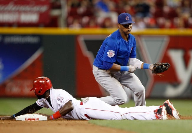 Sep 9, 2013; Cincinnati, OH, USA; Cincinnati Reds second baseman Brandon Phillips (4) goes to second base on a passed ball during the eighth inning against the Chicago Cubs shortstop Starlin Castro (13) at Great American Ball Park. The Cubs defeated the Reds 2-0. Mandatory Credit: Frank Victores-USA TODAY Sports