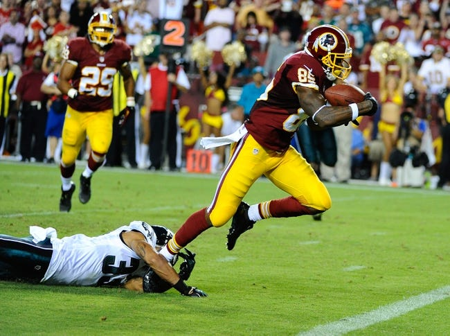 Sep 9, 2013; Landover, MD, USA; Washington Redskins wide receiver Leonard Hankerson (85) breaks the tackle of Philadelphia Eagles cornerback Jordan Poyer (33) to score a touchdown during the second half at FedEX Field. The Eagles won 33 - 27. Mandatory Credit: Brad Mills-USA TODAY Sports