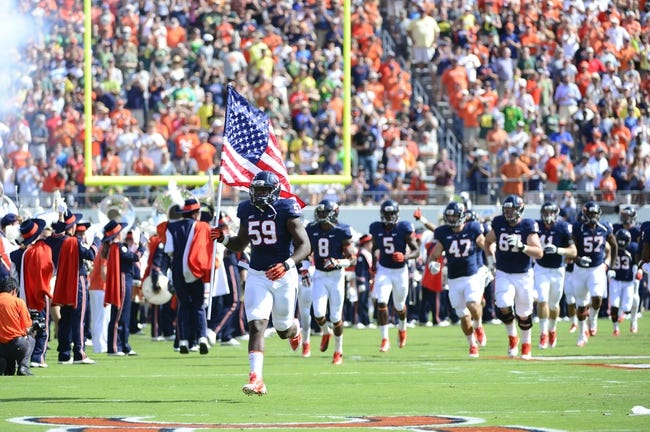 Sep 7, 2013; Charlottesville, VA, USA; Virginia Cavaliers linebacker Mark Hall (59) carries the US flag as he runs on to the field before the game at Scott Stadium. Mandatory Credit: Bob Donnan-USA TODAY Sports