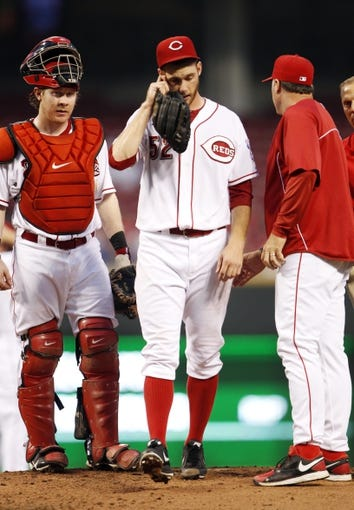 Sep 10, 2013; Cincinnati, OH, USA; Cincinnati Reds pitching coach Bryan Price (right) pulls starting pitcher Tony Cingrani (52) in the second after being injured against the Chicago Cubs at Great American Ball Park. Mandatory Credit: Frank Victores-USA TODAY Sports