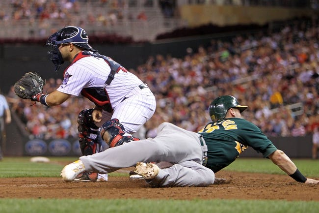 Sep 10, 2013; Minneapolis, MN, USA; Oakland Athletics third baseman Josh Donaldson (20) slides safely around Minnesota Twins catcher Josmil Pinto (43) during the fifth inning at Target Field. Mandatory Credit: Brace Hemmelgarn-USA TODAY Sports