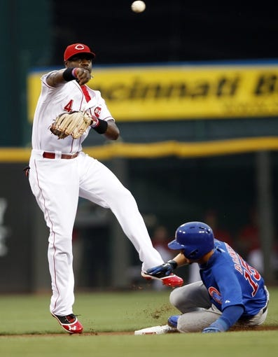 Sep 10, 2013; Cincinnati, OH, USA; Cincinnati Reds second baseman Brandon Phillips (4) attempts a double play during the first inning against the Chicago Cubs second baseman Darwin Barney (15) at Great American Ball Park. Mandatory Credit: Frank Victores-USA TODAY Sports
