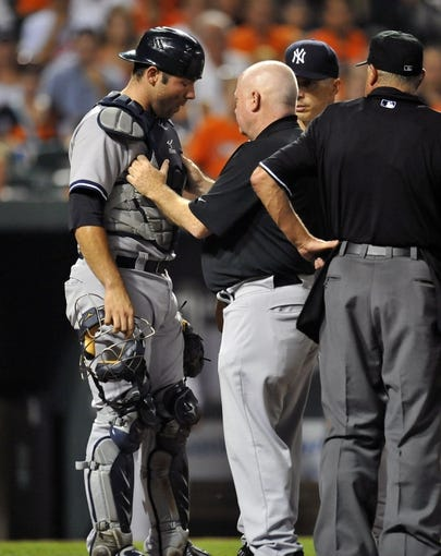 Sep 10, 2013; Baltimore, MD, USA; New York Yankees catcher Austin Romine (53) is tended to by head athletic trainer Steve Donohue after taking a foul ball off his helmet in the eighth inning against the Baltimore Orioles at Oriole Park at Camden Yards. The Yankees defeated the Orioles 7-5. Mandatory Credit: Joy R. Absalon-USA TODAY Sports