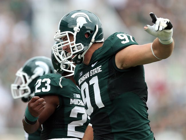 Sep 7, 2013; East Lansing, MI, USA; Michigan State Spartans defensive tackle Tyler Hoover (91) celebrates a defensive stop during the first quarter of a game between the Michigan State Spartans and the South Florida Bulls at Spartan Stadium. Mandatory Credit: Mike Carter-USA TODAY Sports