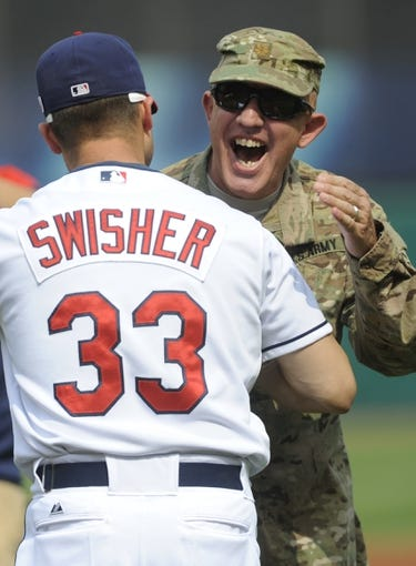 Sep 11, 2013; Cleveland, OH, USA; Cleveland Indians first baseman Nick Swisher (33) and Major James Ruzicka after he threw out the first pitch before the game against the Kansas City Royals at Progressive Field. Mandatory Credit: Ken Blaze-USA TODAY Sports