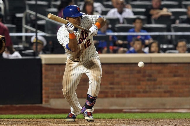 Sep 11, 2013; New York, NY, USA; New York Mets center fielder Juan Lagares (12) lays down a bunt for a single against the Washington Nationals during the ninth inning of a game at Citi Field. Mandatory Credit: Brad Penner-USA TODAY Sports