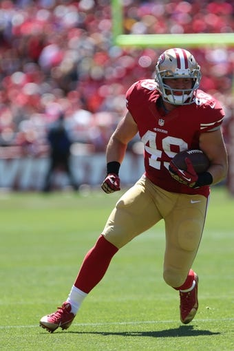 Sep 8, 2013; San Francisco, CA, USA; San Francisco 49ers fullback Bruce Miller (49) carries the ball against the Green Bay Packers during the first quarter at Candlestick Park. Mandatory Credit: Kelley L Cox-USA TODAY Sports