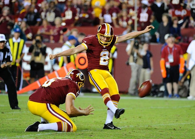 Sep 9, 2013; Landover, MD, USA; Washington Redskins place kicker Kai Forbath (2) attempts an extra point as Washington Redskins punter Sav Rocca (6) holds against the Philadelphia Eagles during the second half at FedEX Field. The Eagles won 33 - 27. Mandatory Credit: Brad Mills-USA TODAY Sports