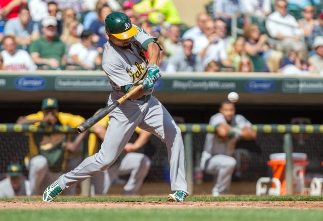 Sep 12, 2013; Minneapolis, MN, USA; Oakland Athletics center fielder Coco Crisp (4) gets a base hit in the fifth inning against the Minnesota Twins at Target Field. Mandatory Credit: Brad Rempel-USA TODAY Sports