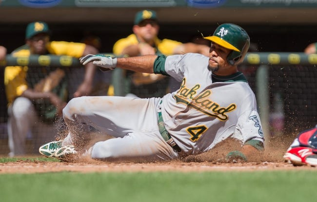 Sep 12, 2013; Minneapolis, MN, USA; Oakland Athletics center fielder Coco Crisp (4) slides safely into home in the fifth inning against the Minnesota Twins at Target Field. Mandatory Credit: Brad Rempel-USA TODAY Sports