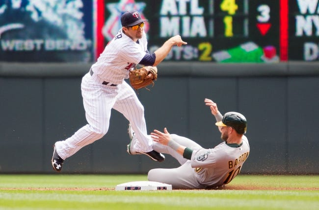 Sep 12, 2013; Minneapolis, MN, USA; Minnesota Twins second baseman Brian Dozier (2) throws the ball to first base to complete a double play over Oakland Athletics first baseman Daric Barton (10) in the third inning at Target Field. Mandatory Credit: Brad Rempel-USA TODAY Sports
