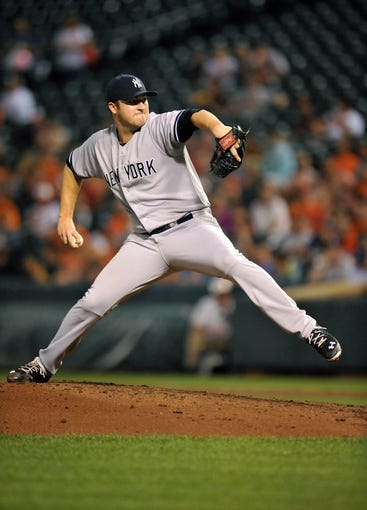 Sep 12, 2013; Baltimore, MD, USA; New York Yankees starting pitcher Phil Hughes (65) throws in the third inning against the Baltimore Orioles at Oriole Park at Camden Yards. Mandatory Credit: Joy R. Absalon-USA TODAY Sports