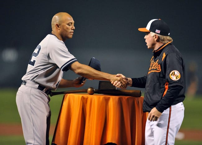 Sep 12, 2013; Baltimore, MD, USA; Retiring New York Yankees pitcher Mariano Rivera (42) is presented with a gift of a broken bat sculpture by Baltimore Orioles manager Buck Showalter (26) prior to a game against the Baltimore Orioles at Oriole Park at Camden Yards. Mandatory Credit: Joy R. Absalon-USA TODAY Sports