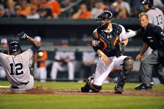 Sep 12, 2013; Baltimore, MD, USA; New York Yankees left fielder Alfonso Soriano (12) is safe at home on a two-run RBI single by New York Yankees right fielder Vernon Wells (not shown) as Baltimore Orioles catcher Matt Wieters (32) does not get the throw in time in the third inning at Oriole Park at Camden Yards. Mandatory Credit: Joy R. Absalon-USA TODAY Sports