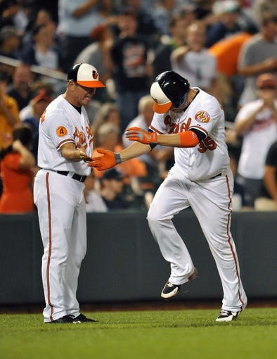 Sep 12, 2013; Baltimore, MD, USA; Baltimore Orioles designated hitter Danny Valencia (35) is congratulated by third base coach Bobby Dickerson (11) after hitting a three-run home run to tie the game in the eighth inning against the New York Yankees at Oriole Park at Camden Yards. The Yankees defeated the Orioles 6-5. Mandatory Credit: Joy R. Absalon-USA TODAY Sports