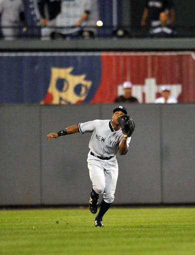 Sep 12, 2013; Baltimore, MD, USA; New York Yankees right fielder Curtis Granderson (14) catches a pop-up by Baltimore Orioles second baseman Brian Roberts (not shown) in the seventh inning at Oriole Park at Camden Yards. The Yankees defeated the Orioles 6-5. Mandatory Credit: Joy R. Absalon-USA TODAY Sports