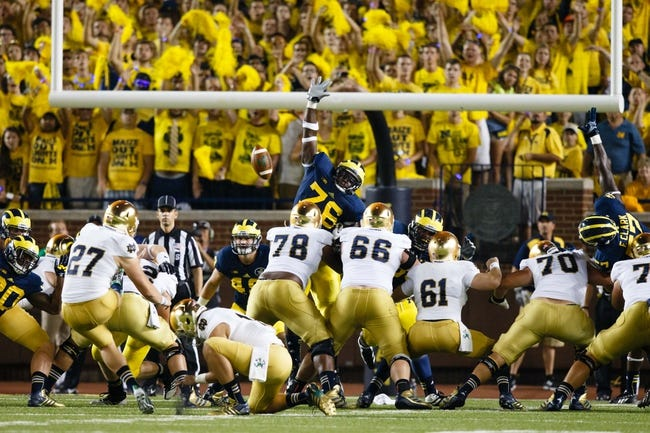 Sep 7, 2013; Ann Arbor, MI, USA; Notre Dame Fighting Irish kicker Kyle Brindza (27) kicks a field goal over Michigan Wolverines defensive tackle Quinton Washington (76) in the first half at Michigan Stadium. Mandatory Credit: Rick Osentoski-USA TODAY Sports