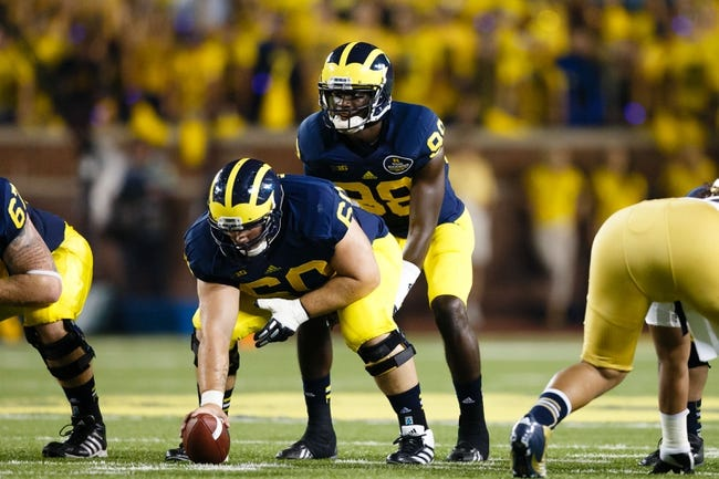 Sep 7, 2013; Ann Arbor, MI, USA; Michigan Wolverines quarterback Devin Gardner (98) gets set to run a play against the Notre Dame Fighting Irish at Michigan Stadium. Mandatory Credit: Rick Osentoski-USA TODAY Sports