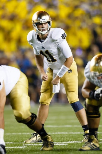 Sep 7, 2013; Ann Arbor, MI, USA; Notre Dame Fighting Irish quarterback Tommy Rees (11) gets set to run a play against the Michigan Wolverines at Michigan Stadium. Mandatory Credit: Rick Osentoski-USA TODAY Sports