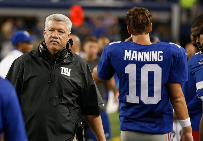 Sep 8, 2013; Arlington, TX, USA; New York Giants offensive coordinator Kevin Gilbride walks past quarterback Eli Manning (10) on the sidelines during the game against the Dallas Cowboys  at AT&T Stadium. The Dallas Cowboys beat the New York Giants 36-31. Mandatory Credit: Tim Heitman-USA TODAY Sports