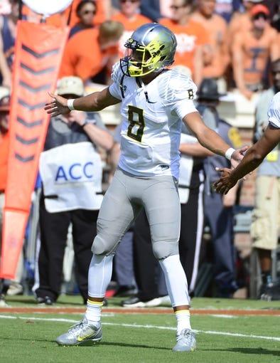Sep 7, 2013; Charlottesville, VA, USA; Oregon Ducks quarterback Marcus Mariota (8) greets players coming off the field at Scott Stadium. Mandatory Credit: Bob Donnan-USA TODAY Sports