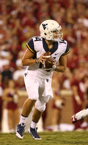 Sep 7, 2013; Norman, OK, USA; West Virginia Mountaineers quarterback Paul Millard (14) scrambles against the Oklahoma Sooners at Gaylord Family - Oklahoma Memorial Stadium. The Oklahoma Sooners beat the West Virginia Mountaineers 16-7. Mandatory Credit: Matthew Emmons-USA TODAY Sports