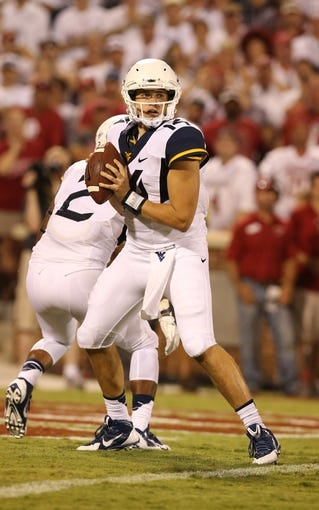 Sep 7, 2013; Norman, OK, USA; West Virginia Mountaineers quarterback Paul Millard (14) throws in the pocket against the Oklahoma Sooners at Gaylord Family - Oklahoma Memorial Stadium. The Oklahoma Sooners beat the West Virginia Mountaineers 16-7. Mandatory Credit: Matthew Emmons-USA TODAY Sports