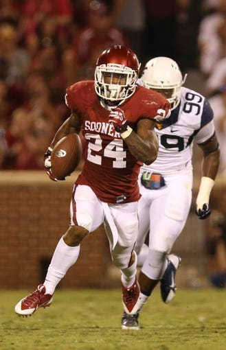 Sep 7, 2013; Norman, OK, USA; Oklahoma Sooners running back Brennan Clay (24) runs with the ball against the West Virginia Mountaineers at Gaylord Family - Oklahoma Memorial Stadium. Mandatory Credit: Matthew Emmons-USA TODAY Sports