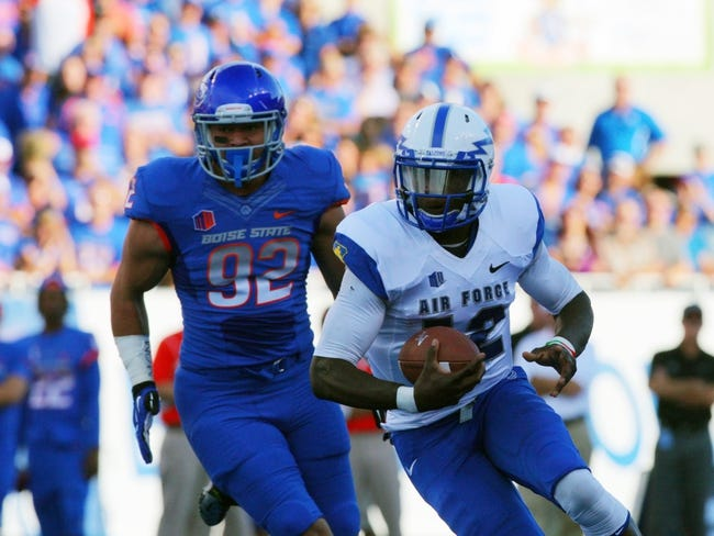 Sep 13, 2013; Boise, ID, USA; Air Force Falcons quarterback Jaleel Awini (12) runs for a gain as Boise State Broncos defensive end Kamalei Correa (92) defends during the first half at Bronco Stadium. Mandatory Credit: Brian Losness-USA TODAY Sports