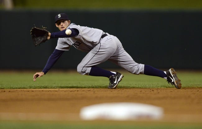 Sep 13, 2013; St. Louis, MO, USA; Seattle Mariners shortstop Brad Miller (5) dives and throws out St. Louis Cardinals third baseman David Freese (not pictured) during the second inning at Busch Stadium. Mandatory Credit: Jeff Curry-USA TODAY Sports