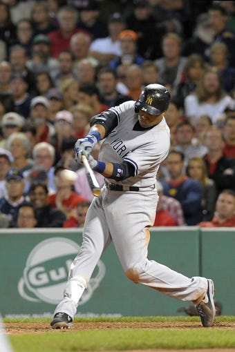 Sep 13, 2013; Boston, MA, USA; New York Yankees second baseman Robinson Cano (24) hits an RBI game tying double during the seventh inning against the Boston Red Sox at Fenway Park. Mandatory Credit: Bob DeChiara-USA TODAY Sports