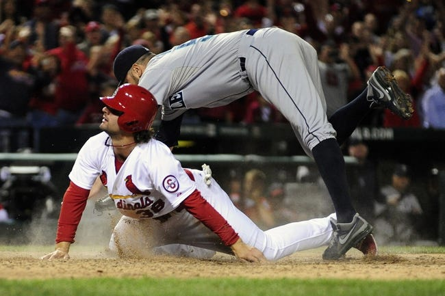 Sep 13, 2013; St. Louis, MO, USA; St. Louis Cardinals shortstop Pete Kozma (38) slides safely past Seattle Mariners relief pitcher Oliver Perez (59) to score on a pass ball during the tenth inning at Busch Stadium. St. Louis defeated Seattle 2-1 in 10 innings. Mandatory Credit: Jeff Curry-USA TODAY Sports