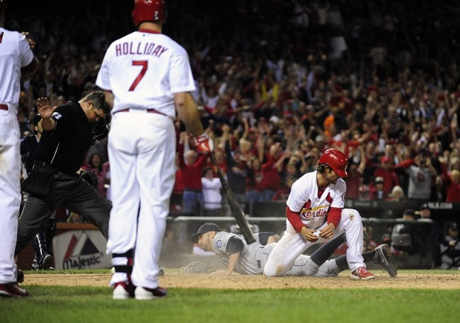 Sep 13, 2013; St. Louis, MO, USA; St. Louis Cardinals shortstop Pete Kozma (38) celebrates after sliding safely past Seattle Mariners relief pitcher Oliver Perez (59) to score on a pass ball during the tenth inning at Busch Stadium. St. Louis defeated Seattle 2-1 in 10 innings. Mandatory Credit: Jeff Curry-USA TODAY Sports